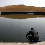 A security guard tries to find the puncture in the inner-tube of his bicycle tire by immersing it in the deserted and unmaintained former course for the kayaking competition of the 2008 Beijing Olympic Games. Picture: REUTERS/David Gray