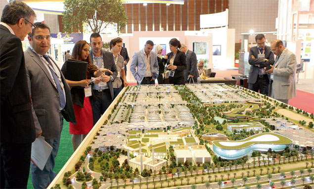 Visitors view the Sustainable City model displayed at Dubai International Property Show.  Source: Kaleej Times