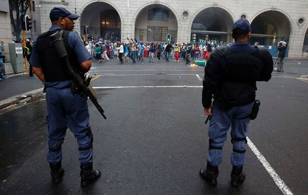 Police stand guard as protestors demonstrate against a lack of housing and other services outside provincial government buildings in central Cape Town, October 30, 2013.  Image by: MIKE HUTCHINGS / REUTERS