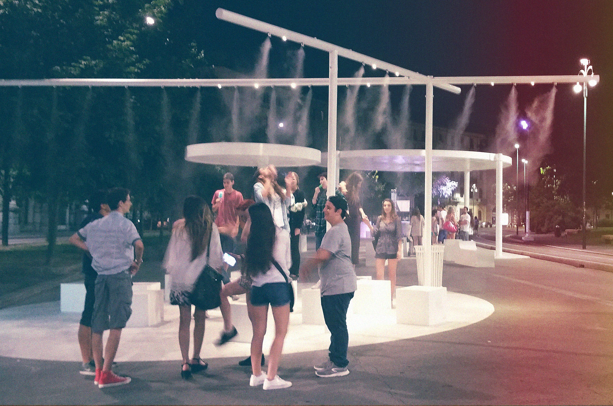 A warm summer night. People refreshing with #nevicata14 misting systems.